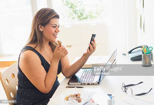 USA, New Jersey, Jersey City, Woman eating croissant and using mobile phone in office
