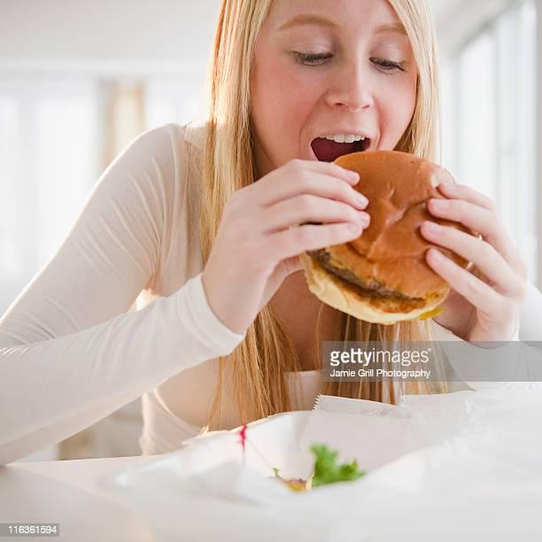 USA, New Jersey, Jersey City, woman eating hamburger