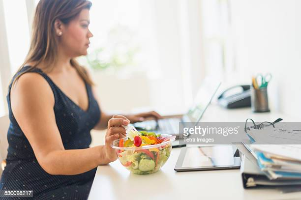 usa, new jersey, jersey city, woman eating salad and using laptop in office - grasa nutriente fotografías e imágenes de stock