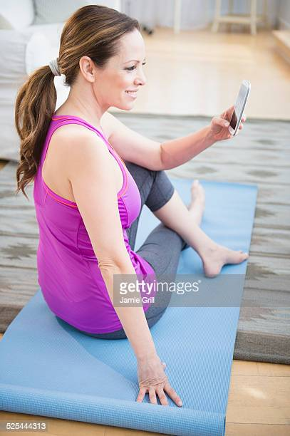 USA, New Jersey, Jersey City, Woman exercising and holding mobile phone