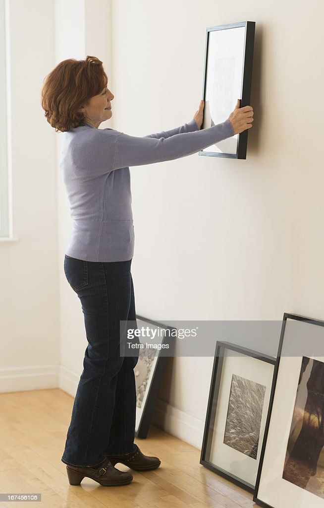 USA, New Jersey, Jersey City, Woman hanging picture on wall : Stock Photo
