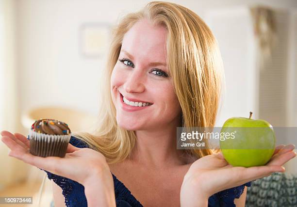 USA, New Jersey, Jersey City, Woman holding apple and cupcake