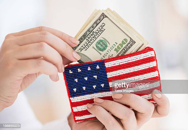 USA, New Jersey, Jersey City, Woman holding banknotes and purse with american flag on it
