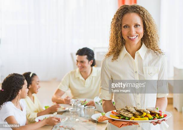 USA, New Jersey, Jersey City, Woman holding dinner plate, with husband and daughters (10-13) in background