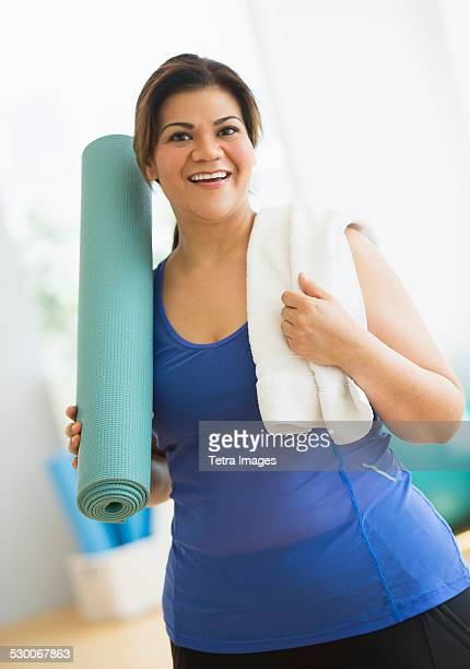 USA, New Jersey, Jersey City, Woman holding exercise mat at gym