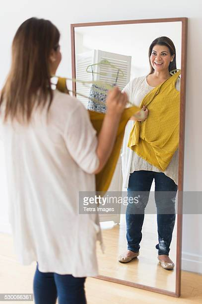 USA, New Jersey, Jersey City, Woman holding new dress and looking at mirror