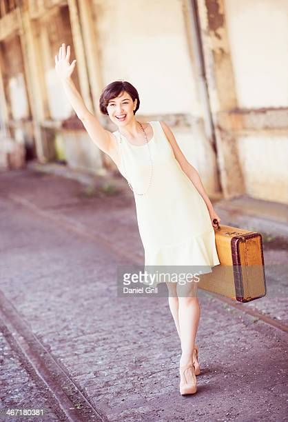 usa, new jersey, jersey city, woman in dress holding suitcase at train station, waving hand - sleeveless stock pictures, royalty-free photos & images