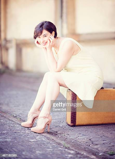USA, New Jersey, Jersey City, Woman in dress sitting on suitcase at train station