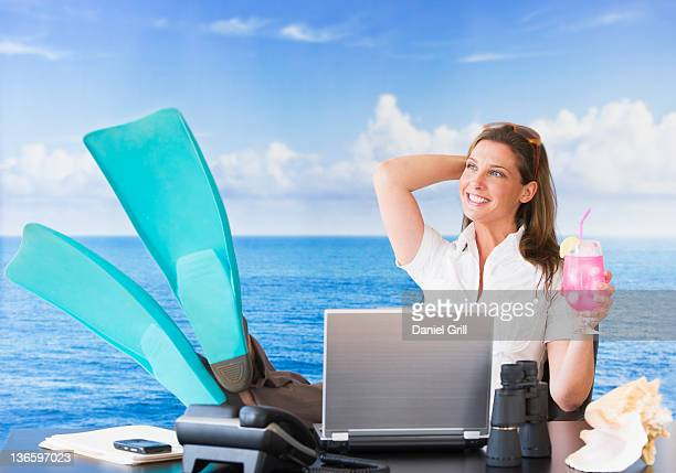 usa, new jersey, jersey city, woman in flippers daydreaming at desk - fake photos et images de collection