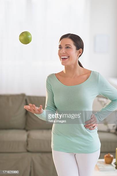 USA, New Jersey, Jersey City, Woman juggling with apple at home