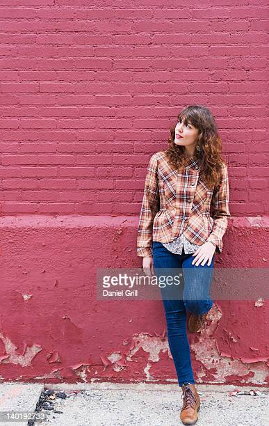 USA, New Jersey, Jersey City, Woman leaning against purple brick wall