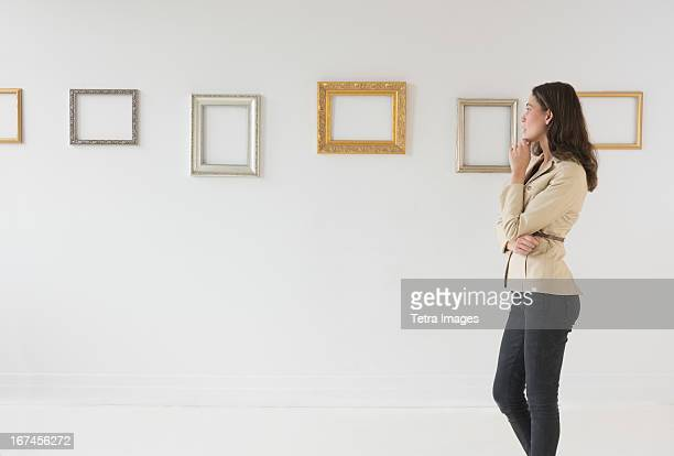USA, New Jersey, Jersey City, Woman looking at blank pictures in art gallery
