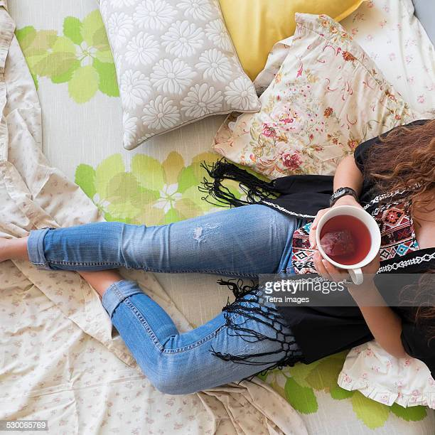 usa, new jersey, jersey city, woman lying down on bed with tea cup - down blouse stock pictures, royalty-free photos & images