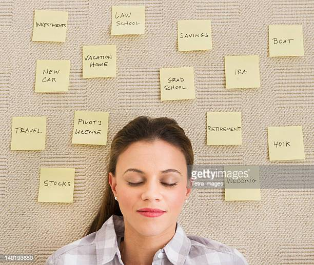 USA, New Jersey, Jersey City, Woman lying on carpet with adhesive notes around head