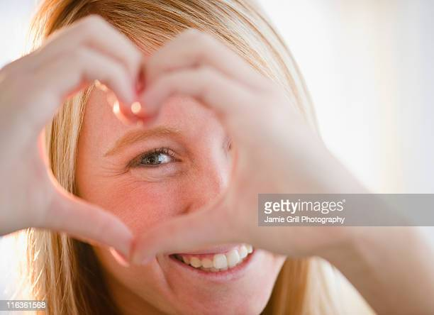 USA, New Jersey, Jersey City, woman making heart shape with fingers