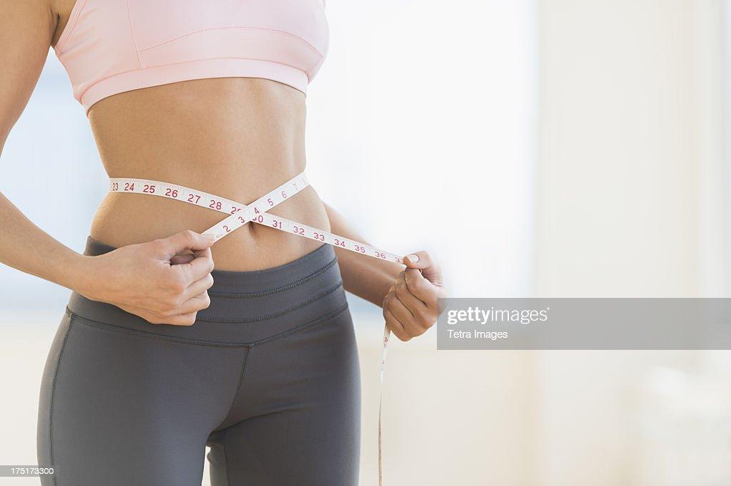 USA, New Jersey, Jersey City, Woman measuring waist : ストックフォト