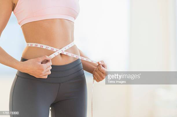 usa, new jersey, jersey city, woman measuring waist - medir imagens e fotografias de stock