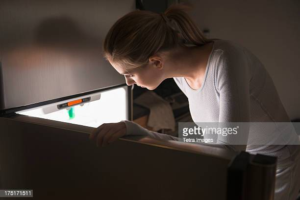 USA, New Jersey, Jersey City, Woman opening fridge at night