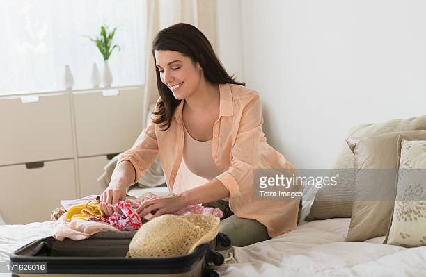 USA, New Jersey, Jersey City, Woman packing suitcase in bedroom