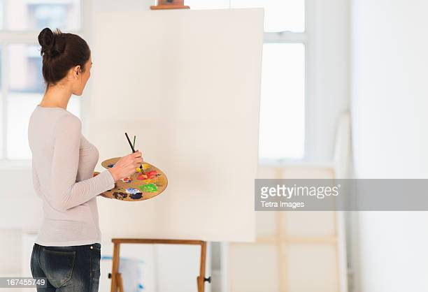 usa, new jersey, jersey city, woman painting at easel - easel stock pictures, royalty-free photos & images
