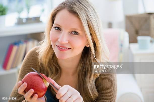 USA, New Jersey, Jersey City, Woman peeling apple