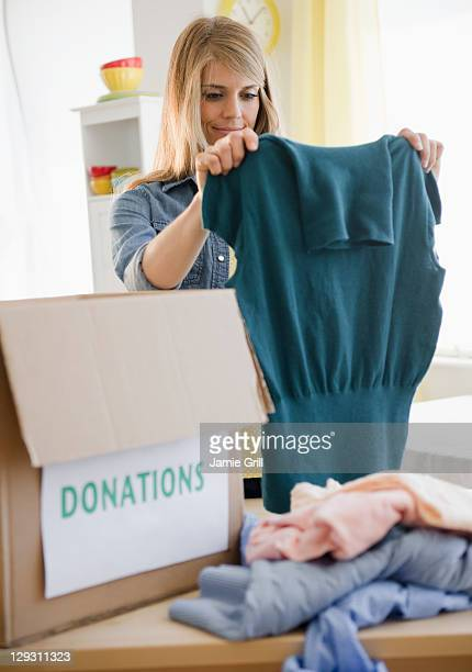 usa, new jersey, jersey city, woman preparing clothes for donation - donation stock photos and pictures