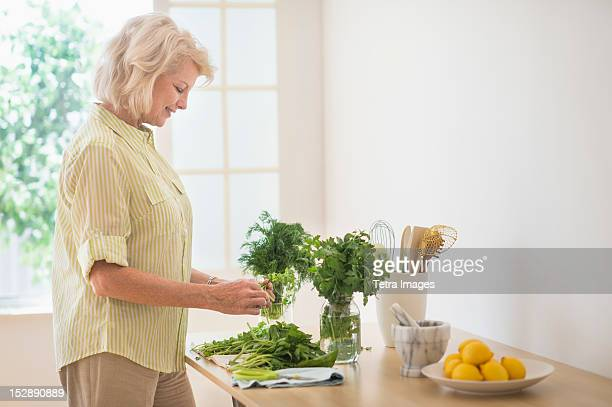 USA, New Jersey, Jersey City, Woman preparing food in kitchen