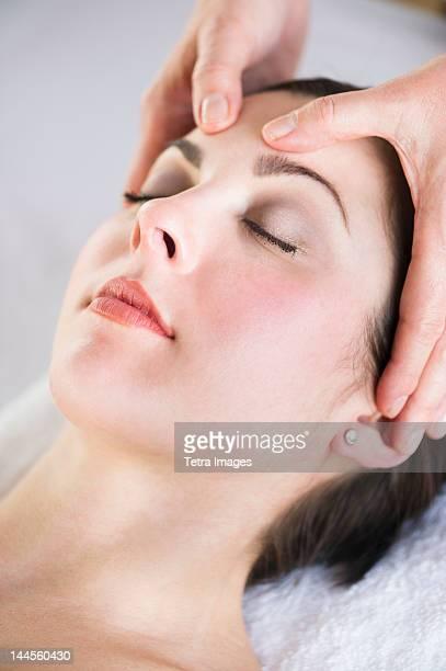 usa, new jersey, jersey city, woman receiving face massage - druckpunkt stock-fotos und bilder