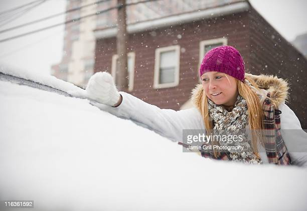 USA, New Jersey, Jersey City, woman removing snow from wind shield