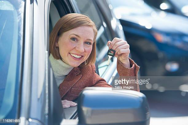 USA, New Jersey, Jersey City, woman sitting in new car showing car key