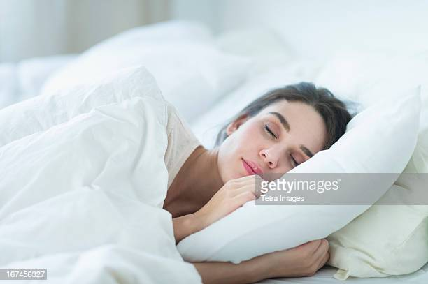usa, new jersey, jersey city, woman sleeping in bed - slapen stockfoto's en -beelden