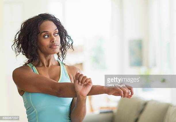 USA, New Jersey, Jersey City, Woman stretching in living room