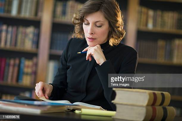 USA, New Jersey, Jersey City, woman studying at desk in library