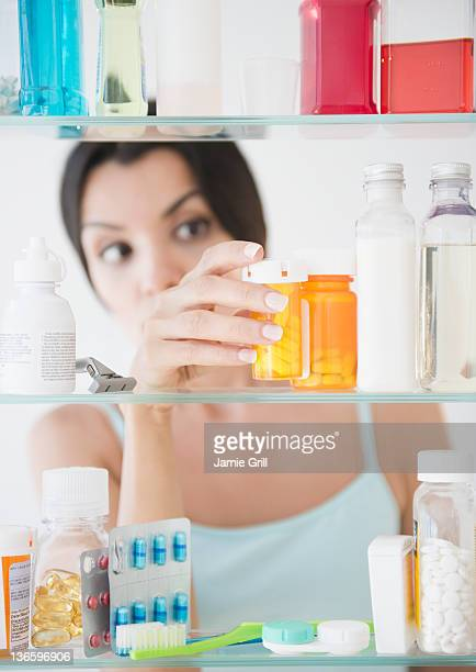 USA, New Jersey, Jersey City, Woman taking medicine from cabinet
