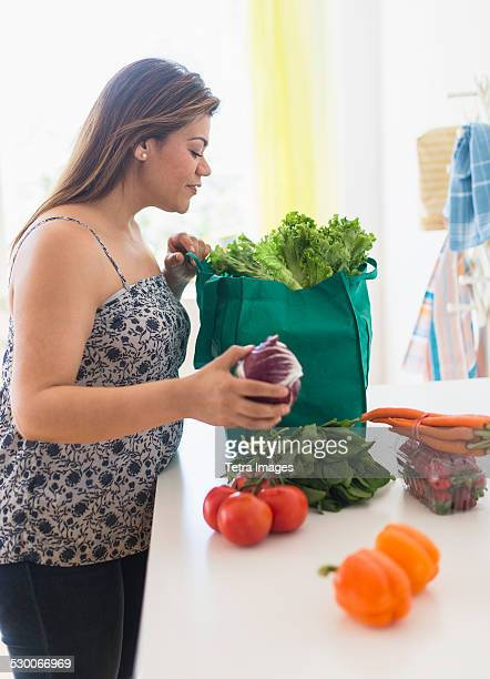 usa, new jersey, jersey city, woman taking out vegetables of grocery bag - fat nutrient stock pictures, royalty-free photos & images