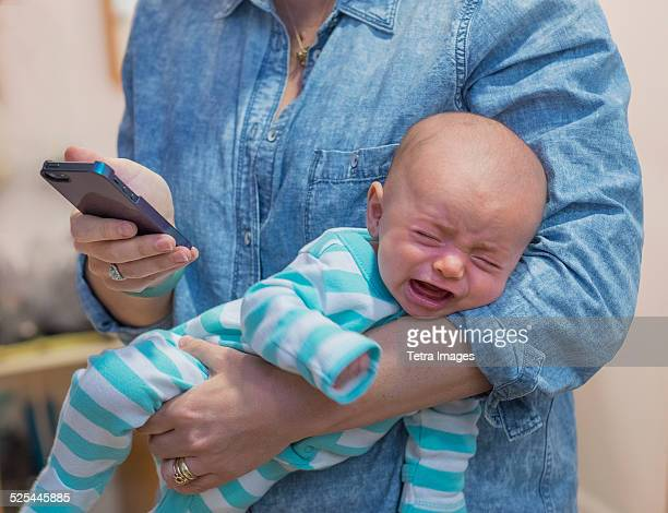 USA, New Jersey, Jersey City, Woman texting and holding crying baby boy (2-5 months)