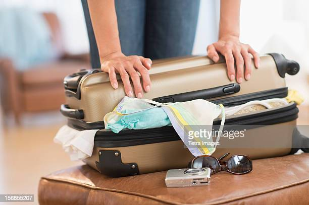 USA, New Jersey, Jersey City, Woman trying to close full suitcase