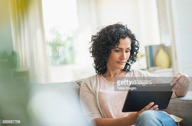 USA, New Jersey, Jersey City, Woman using digital tablet on sofa