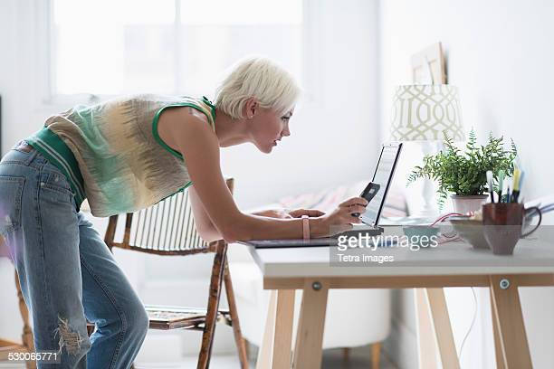 usa, new jersey, jersey city, woman using laptop and cell phone at home - una sola mujer joven fotografías e imágenes de stock