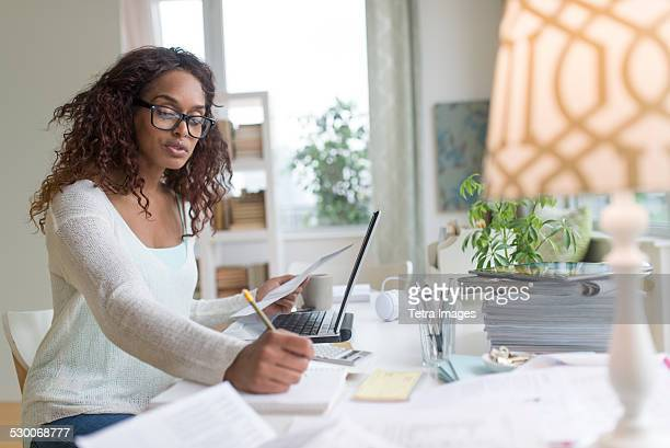 usa, new jersey, jersey city, woman using laptop at home - home finances stock pictures, royalty-free photos & images
