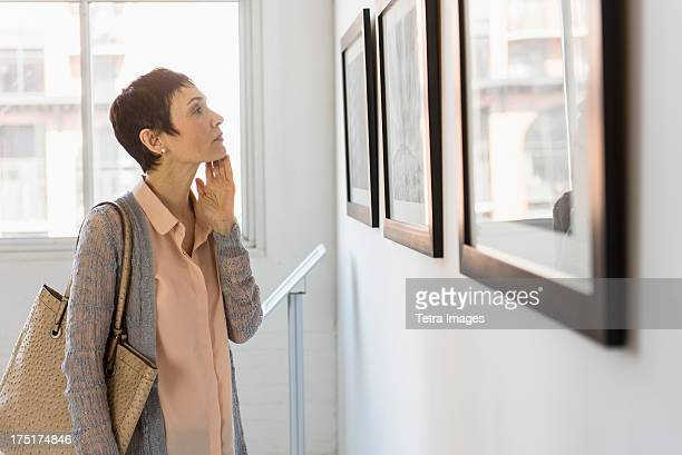 USA, New Jersey, Jersey City, Woman watching photographs in art gallery