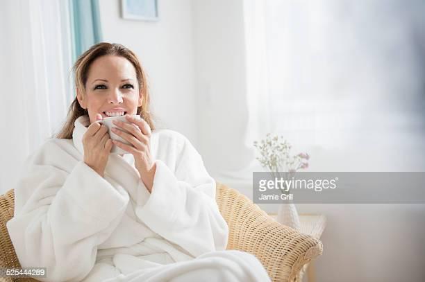 USA, New Jersey, Jersey City, Woman wearing bathrobe drinking tea