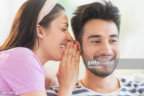 USA, New Jersey, Jersey City, Woman whispering to man's ear