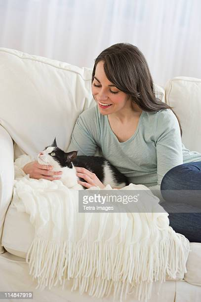 USA, New Jersey, Jersey City, woman with cat on sofa