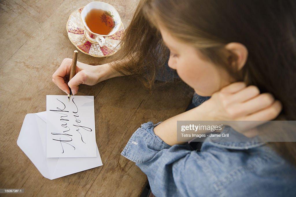 USA, New Jersey, Jersey City, Woman writing greeting card : Stock Photo