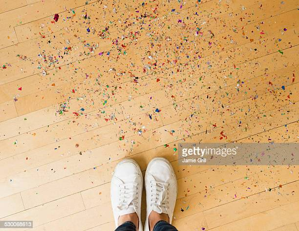 USA, New Jersey, Jersey City, Woman's feet and confetti on floor