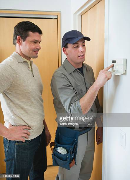 USA, New Jersey, Jersey City, worker and house owner setting up security system