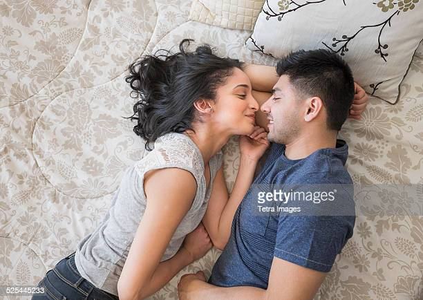 USA, New Jersey, Jersey City, Young couple lying on bed