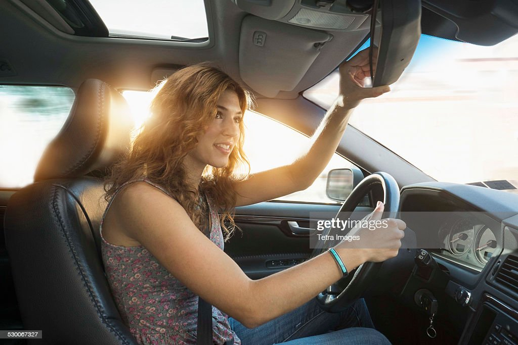 USA, New Jersey, Jersey City, Young woman adjusting rear view mirror while driving : Stock Photo