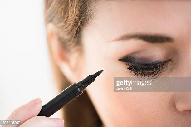 usa, new jersey, jersey city, young woman applying eyeliner - aplicando - fotografias e filmes do acervo